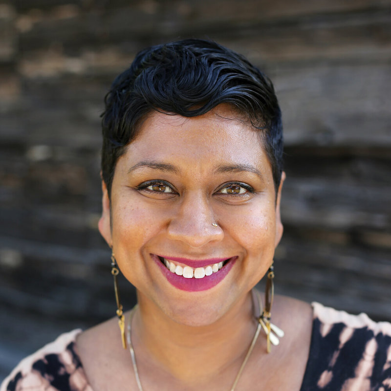 Anisha smiling into the camera wearing long, dangly earrings and a dark and light brown shirt.